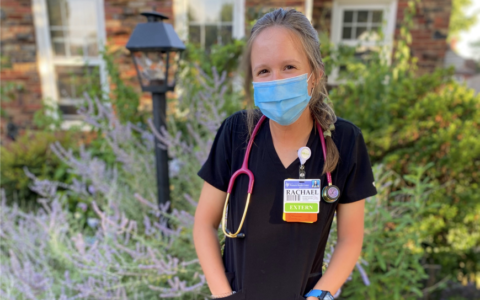 Bachelor of science student Rachael Shewey wearing hospital scrubs and a face mask outdoors